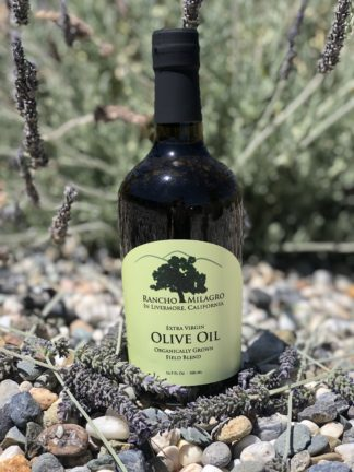 Rancho Milagro olive oil bottle resting on lavender flowers